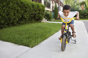 Young-boy-rides-his-yellow-bicycle-down-a-sidewalk-000013650330_Medium